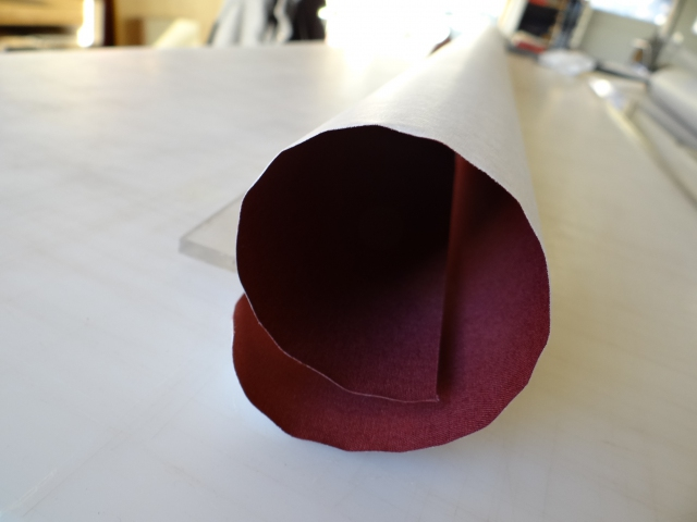 Burgundy book cloth, severely curled from being stored on the roll
