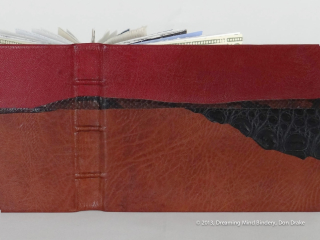 A detail view of Don Drake's binding of the Bay Area Book Artists' (BABA) collaborative project, AlphaBeastiary, showing the goat, snake, and alligator leather.