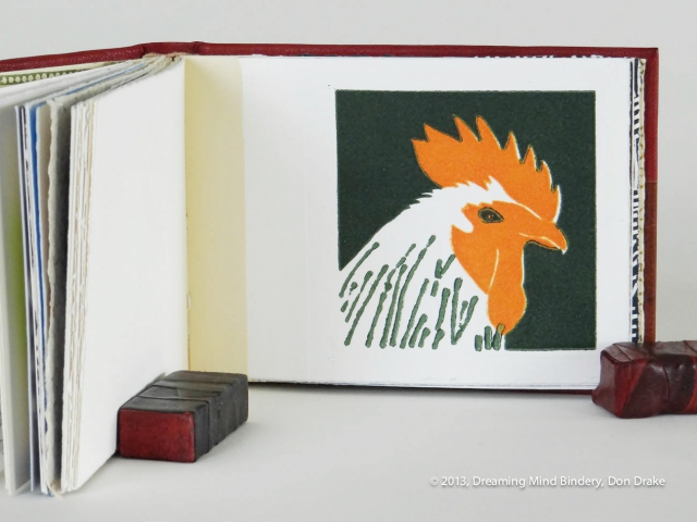 An interior view of Don Drake's binding of the Bay Area Book Artists' (BABA) collaborative project, AlphaBeastiary, showing the 'R' page (rooster). This page was created and printed by Rae Trujillo.