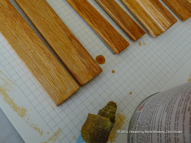 Applying amber shellac to the oak rails of a custom box.