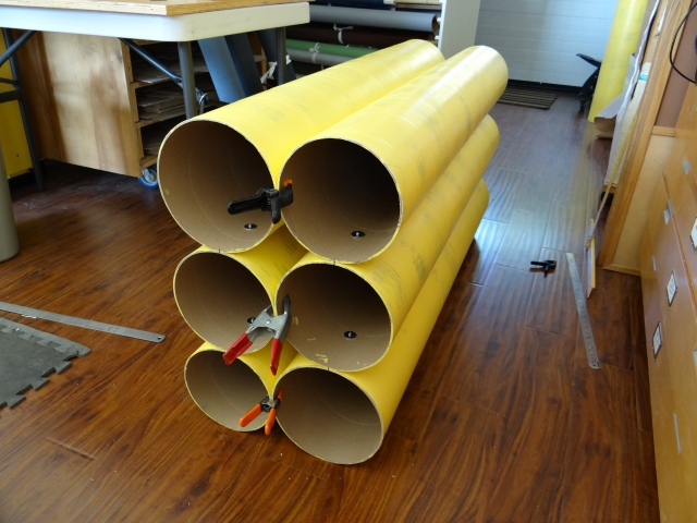 Assembling the first bank of six cardboard tubes during construction of a roll material storage unit.