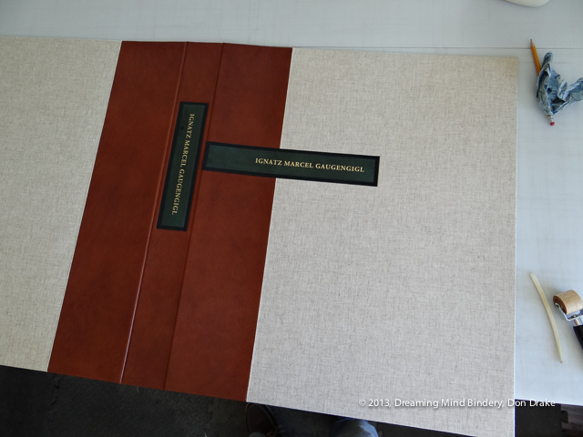 The labels placed in the debossed beds in a cloth and leather portfolio lid