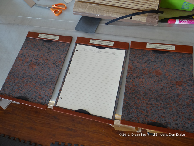 3 leather and marbled paper sign-in station boards, one with the guest pages in place.