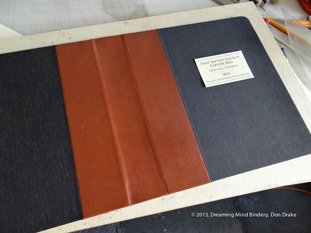 Cover of a cloth and leather notebook with a lacquered paper label laying on it while checking for size.