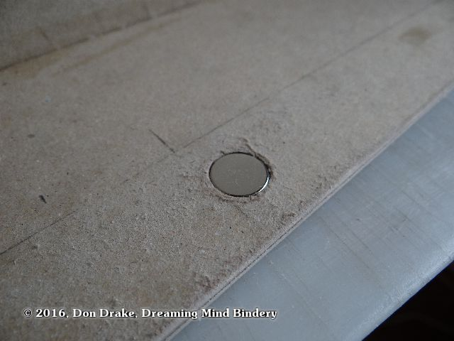 Rare earth magnet set into a hole in a box wall