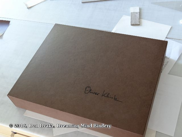 The exterior of Oliver Klink's clamshell box showing the brown covering material and black foil stamped signature.