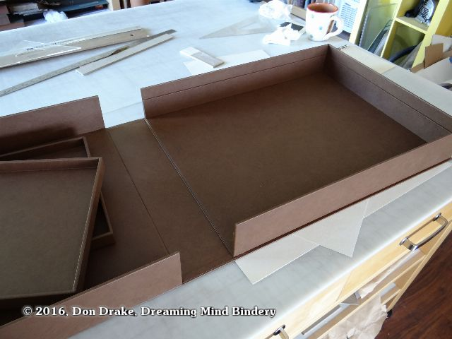 The interior of a clamshell box with trays showing the trays removed and revealing the rails that support them