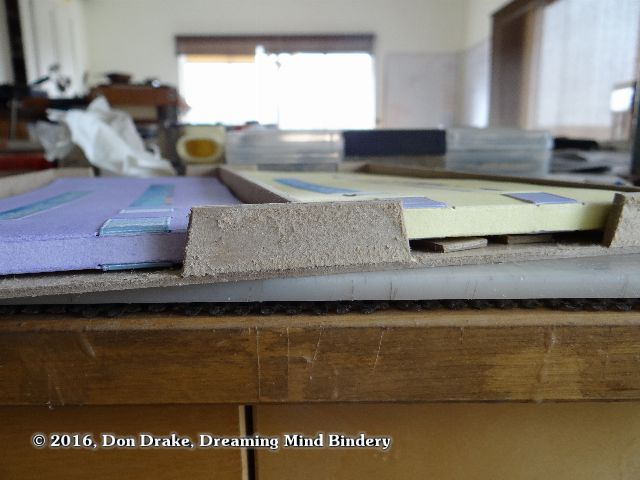 And end view of a box showing two books, one lifted on shims to estimate the bottom liner that should be constructed.