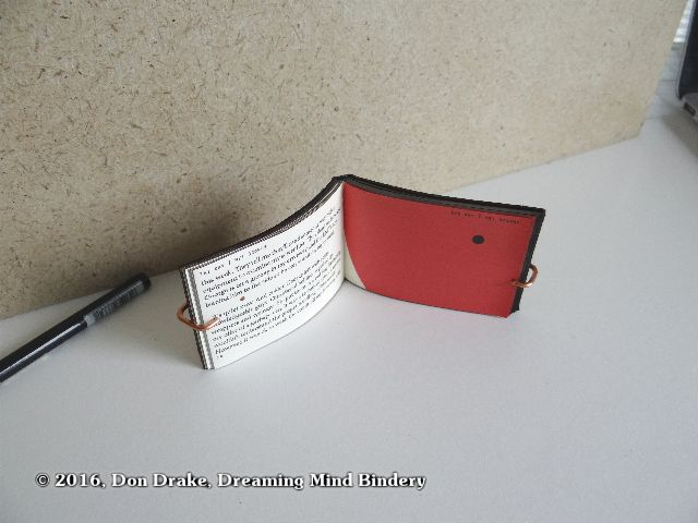 A miniature book being held open with a wire bracket to allow photographing its interior