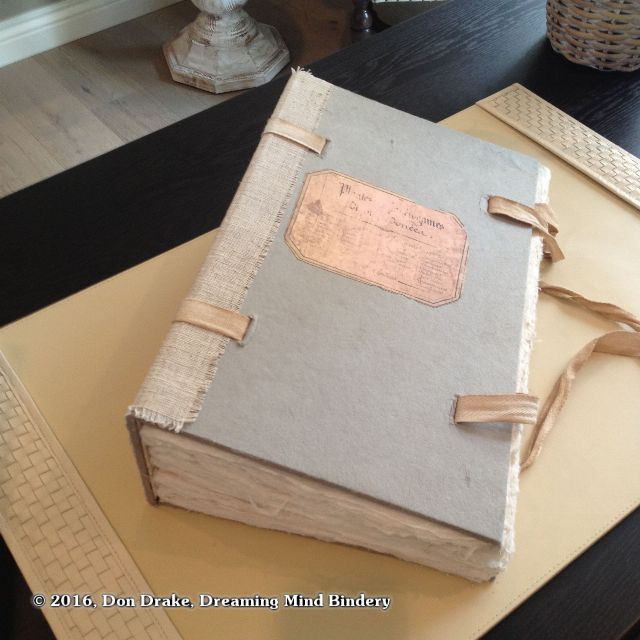 A large, hand bound blank book filled with handmade paper