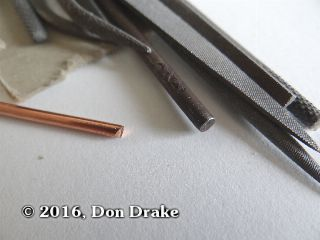 The end of a piece of copper wire showing the sharp end after cutting it to length. Also show are the jewelers files that will be used to take the sharp edges off.